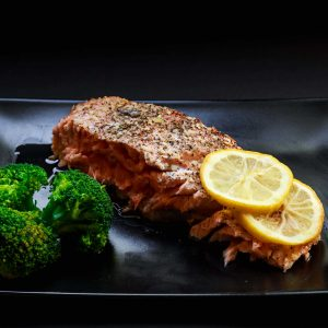 Grilled salmon on a black plate with two slices of lemon and broccoli.