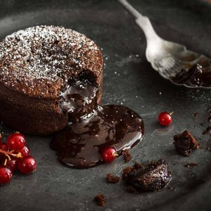 A single serving of warm chocolate lava cake sprinkled with powdered sugar with a bite taken out. The molten chocolate center spills out through the hole in the cakey wall. Red currant berries are the garnish for this indulgent dessert on a vintage metal plate.