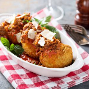 Lasagna balls with crunchy crust, tomato sauce and parmesan shavings