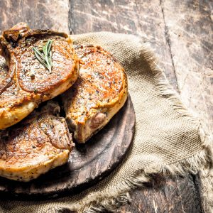 Grilled pork steak with spices. On wooden background.